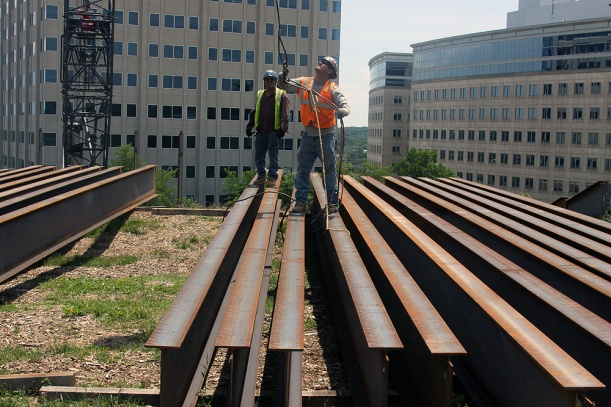 A construction team prepares to hoist a girder as work continues on DHCD's new headquarters building in New Carrollton.
