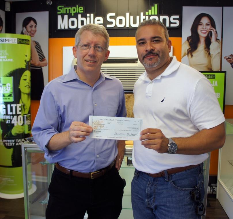 DHCD's John Maneval presents check to business owner Juan C. Nunez
